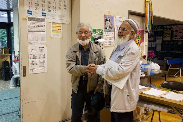 被災者と握手するイスラム教徒